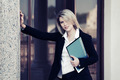Happy young business woman with a folder at office building - PhotoDune Item for Sale