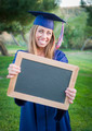 Excited Young Woman Holding Diploma and Blank Chalkboard Wearing Cap and Gown Outdoors. - PhotoDune Item for Sale