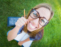 Fun Wide Angle Portrait of Pretty Young Woman with Books and Pencil Sitting in the Grass Outdoors. - PhotoDune Item for Sale