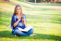 Smiling Young Woman with Book and Cell Phone Outdoors at the Park. - PhotoDune Item for Sale
