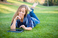 Smiling Young Woman Using Computer Tablet Outdoors at the Park. - PhotoDune Item for Sale