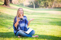 Laughing Young Woman with Book and Cell Phone Outdoors at the Park. - PhotoDune Item for Sale