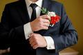 Wedding details, cufflinks, elegant male suit and hands