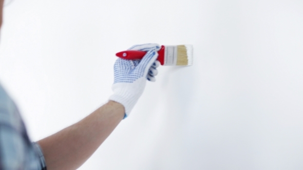 Man Painting With Brush And White Paint