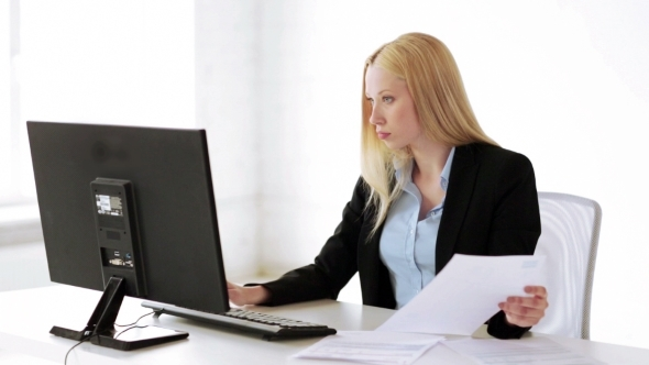 Businesswoman With Computer And Papers At Office