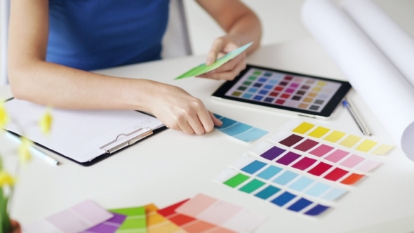 Woman Laying Out Color Palettes On Table