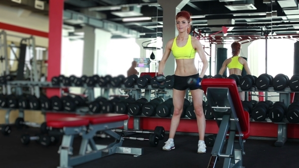 Slender Girl Training With Dumbbells In Gym