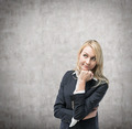 Beautiful blonde business woman is thinking about business issues.Concrete wall background. - PhotoDune Item for Sale