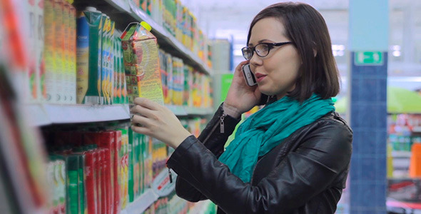The Woman Speaks On The Phone In The Store