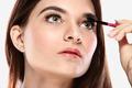 beautiful caucasian model applying mascara