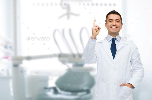 smiling male dentist pointing finger up
