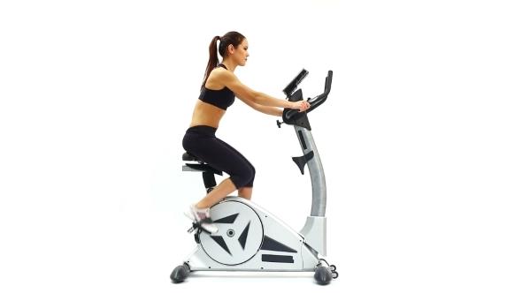 Slender Brunette Training On Bike Exerciser