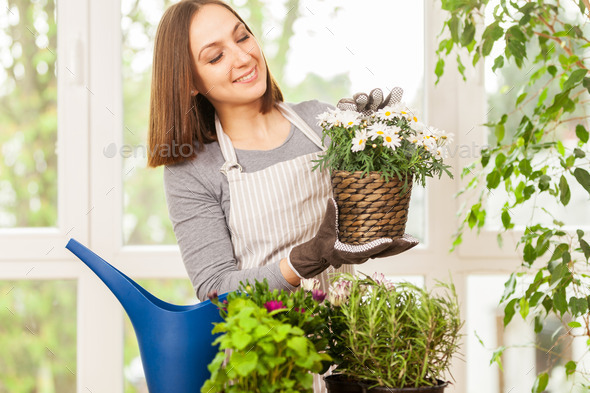 Caucasian young woman doing some gardening at home with her colo
