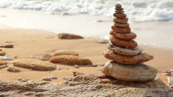 Pyramid of Stones on the Background of the Surf