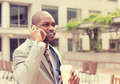 handsome happy businessman talking on mobile phone drinking coffee
