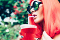 Woman in red wig and black bikini drinking cocktail