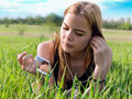 young blond woman listening to music with headphones outdoors - PhotoDune Item for Sale