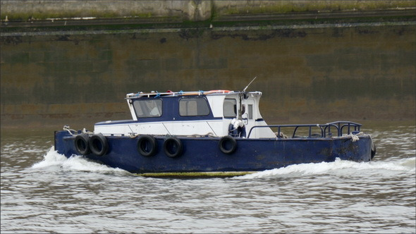 A Blue Small Ferry Boat Crossing the Thames River