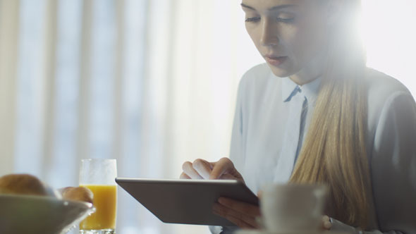 Girl is Using Tablet PC at Breakfast