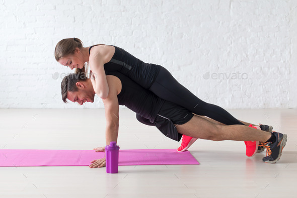 man doing push ups with woman laying on back at gym