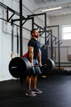 Weightlifter lifting barbells at gym