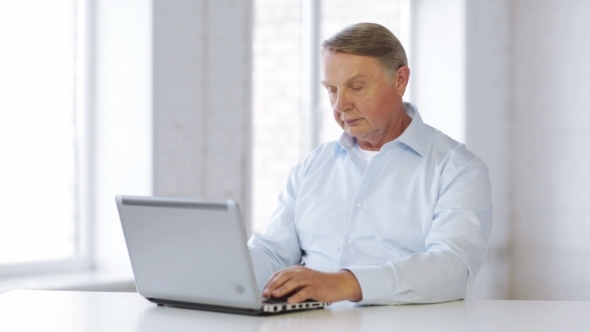 Senior Man Working With Laptop At Home