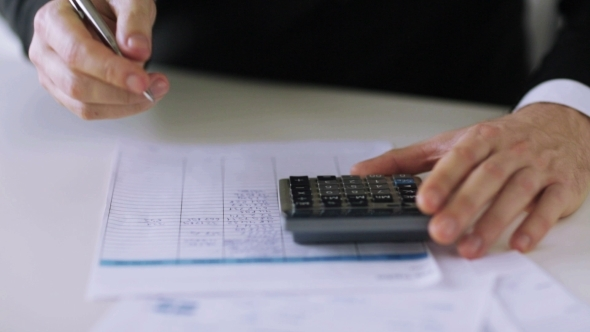 Hands Counting On Calculator And Filling Papers