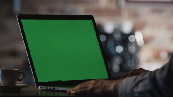 VideoHive Man using Laptop with Green Screen in Cafe 11477400