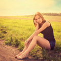 Young sensual smiling blond woman sitting on the grass outdoors - PhotoDune Item for Sale