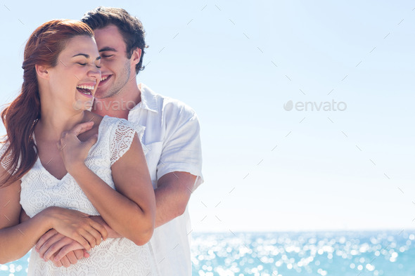 Happy couple hugging and laughing together at the beach