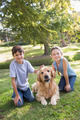 Sibling with their dog in the park on a sunny day