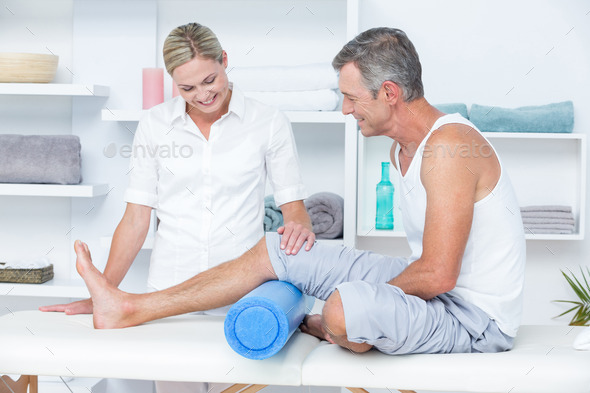 Doctor examining her patient leg in medical office