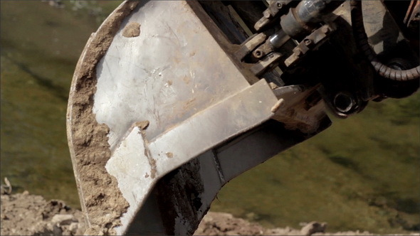 Backhoe Carrying Some Soil and then Dropping it of