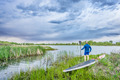 senior paddler with SUP paddleboar watching stormy sky - PhotoDune Item for Sale