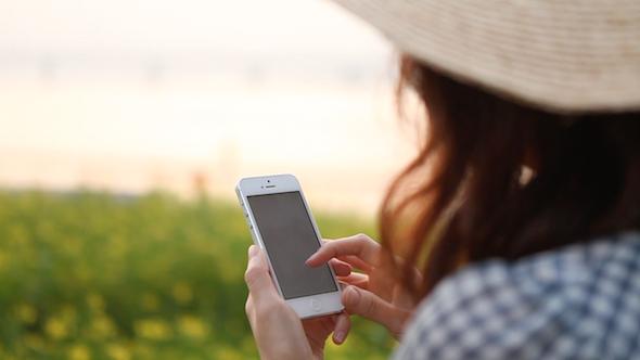 Girl Using Smart Phone Near The Flower Garden