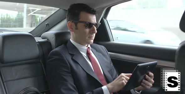 Businessman In Car Using Tablet
