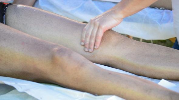 Physiotherapist Massaging Leg of an Athlete
