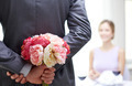 close up of man hiding flowers behind from woman - PhotoDune Item for Sale