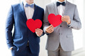 close up of male gay couple holding red hearts - PhotoDune Item for Sale