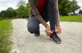 close up of woman tying shoelaces outdoors - PhotoDune Item for Sale