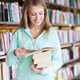 happy student girl or woman with book in library - PhotoDune Item for Sale
