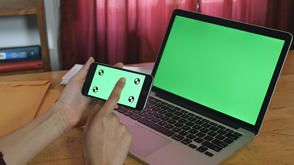 Girl Using her Phone with Green Screen Laptop