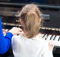 Woman teaching little girl to play the piano. Back view. - PhotoDune Item for Sale