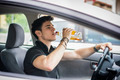 Young man driving his car while drinking alcohol - PhotoDune Item for Sale