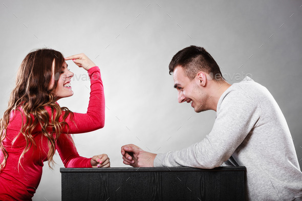 Girl gesturing with finger sitting in front of man