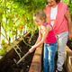 Woman with child grows harvest in the greenhouse - PhotoDune Item for Sale