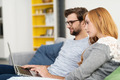 Couple Using Laptop Computer Together on Sofa - PhotoDune Item for Sale