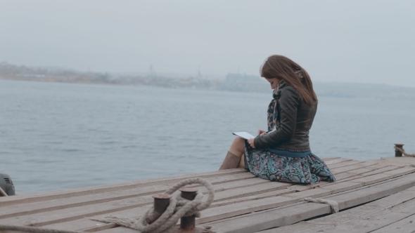 Romantic Girl In Skirt Sitting On The Pier Near