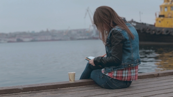 Absorbed In Drawing Girl Sitting On a Wooden Pier