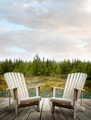 Wooden deck with chairs and forest in background - PhotoDune Item for Sale